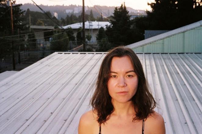 Maria Maita-Keppeler stands on a flat metal roof