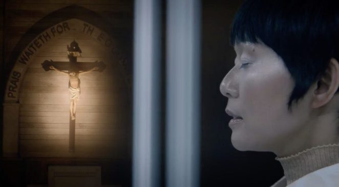 The profile of Lady Trieu next to a crucifix on the wall