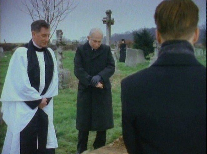 Mrs Drablows funeral with only Mr Kidd, the estate agent and vicar in attendance. A woman in black lurks in the background