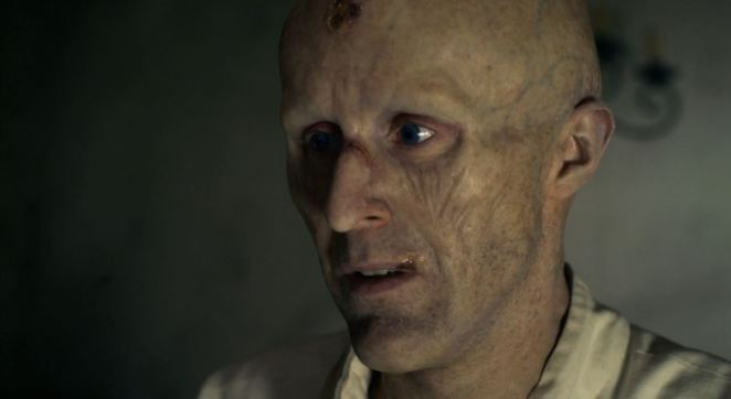 Jonathan Harker is bald with a wrinkled face as he looks on pensively