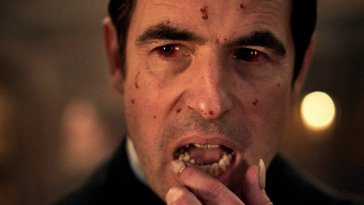 Claes Bang as Dracula wipes his lip with a finger
