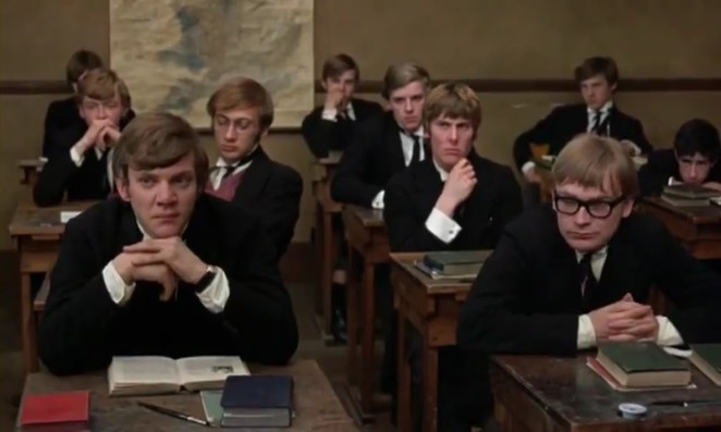 A group of public schoolboys sit at their desk and stare at the front of the classroom