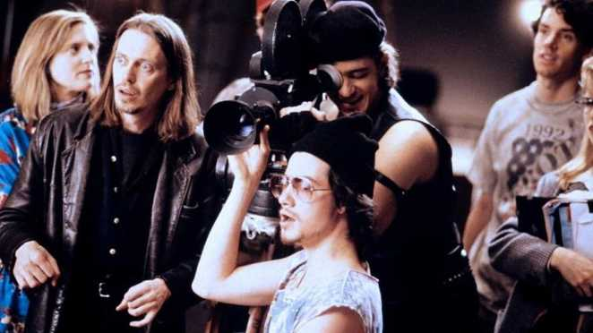 Wanda, Nick, the Assistant Cameraman, and Wolf stand around the camera, shooting a scene