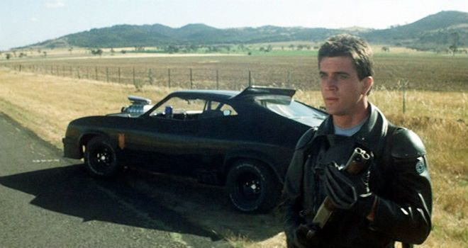 """""""Mad"""" Max Rockatansky holds his gun while standing next to his black vehicle"""