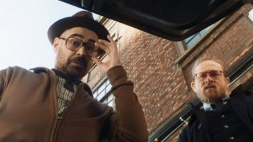 Two men with glasses look down into the trunk of a car