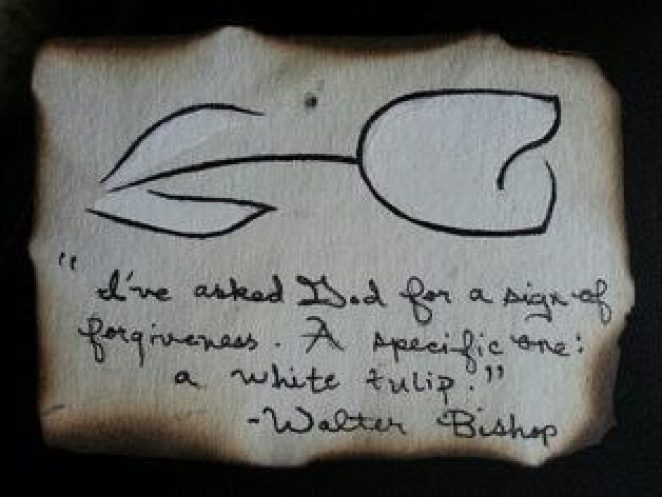 A burned piece of paper with a message about a white tulip inscribed on it.