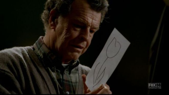 Walter Bishop looking at a picture of a white tulip