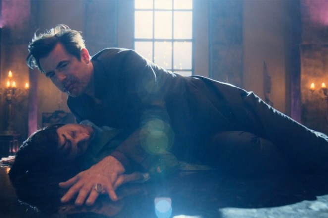 Dracula lies on top of a woman