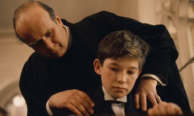 A priest massages a schoolboy's shoulders