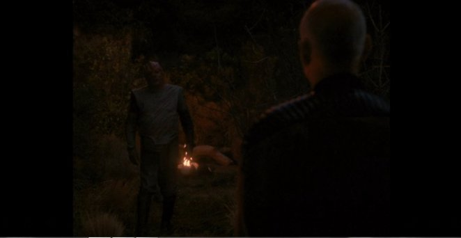 Dathon stands before a fire as he approaches Picard