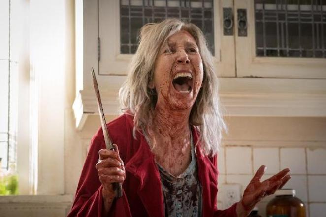 A bloodied woman standing in a kitchen screaming with a knife in her hand