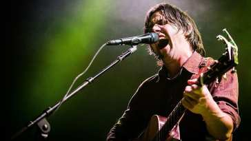 Conor Oberst playing guitar live, singing with his eyes closed
