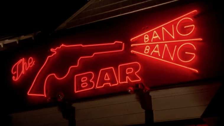 A neon sign, all in red. A pistol on the left, shooting the words Bang and Bang in a triangle shape. The word Bar is centered below them.