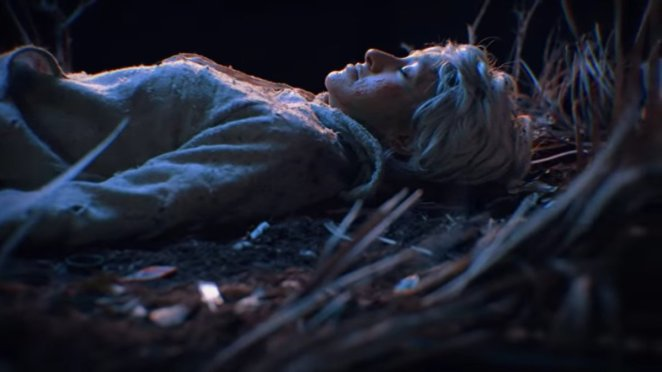 """A woman lies on the forest floor next to a tree in the video for """"Sat by a Tree"""""""