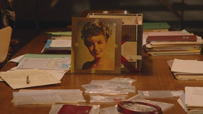The famous prom picture of Laura Palmer is propped up against a storage box, surrounded by pieces of evidence