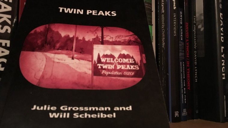The book face out against a bookshelf background. The cover is black, with text in white, and sepiatone image of the Twin Peaks road and population sign on the side.