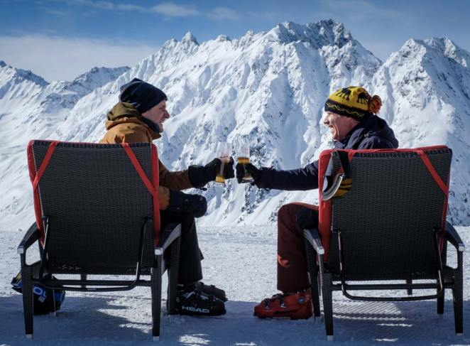 Zach and Pete sit in front of a mountain, clinking glasses of beer together