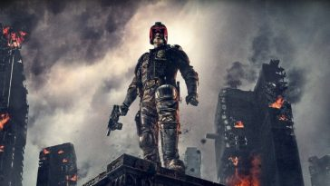 Dredd stands on a buildings edge with gun in hand surrounded by burning buildings