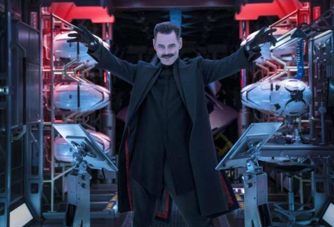 Dr. Robotnik raises his arms in a small room surrounded by drones