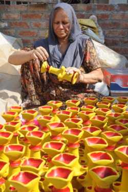 Earthen lamps painted by labourers for Diwali