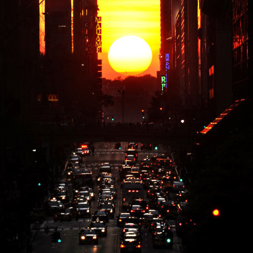 """Natural Occurrence of the Day: The semiannual solar phenomenon known as """"Manhattanhenge"""" — wherein the sunset aligns with the east-west streets of Manhattan's main street grid — took place yesterday at precisely 8:17 PM. Above: Manhattanhenge, as observed from 42nd Street. [telegraph.]"""
