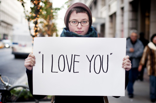 "An image of a young woman holding a sign that says ""I love you"" in large letters"