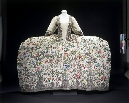 "Court mantua ca. 1740-1745 via The Victoria & Albert Museum ""Object Type 'Court dress' was an exclusive and very ornate style of clothing worn by the aristocracy, the only people usually invited to attend at Court. The style of the robe is quite old-fashioned, and based on the 17th-century mantua. Designs & Designing The shell, the quintessential Rococo motif, constitutes the basis of the embroidery pattern. Leafy scrolls, latticed arcades and tassels are also featured, as well a profusion of realistically rendered flowers, including jasmine, morning glory and honeysuckle, peonies, roses, poppies, anemones, auriculas, hyacinths, carnations, cornflowers, tulips and daffodils. The pattern of the silver shells and scrolls has been arranged symmetrically at the hem, but the layout of the flowers, while balanced, does not match exactly on either side. This ensemble recalls a garment worn by the Duchess of Queensbury in 1740: 'her cloathes were embroidered upon white satin; Vine leaves, Convulvus and Rosebuds shaded after Nature …'. Materials & Making Seven panels of ivory-ribbed silk make up the petticoat. The robings, sleeve cuffs and skirt of the mantua are embroidered in the same design, but were modified to fit their exact proportions. The flowers are worked in a variety of coloured silks in satin stitch and french knots. Silver thread delineates the leaves and the non-floral components of the pattern. Some of the scrolls and border elements have a backing of parchment, for solidity and regularity of line. The tassels and bases of the shells have been thickly padded underneath. Varying the height of the padding under the embroidery of the silver leaves gives the surface of the stitching a rippled effect."""