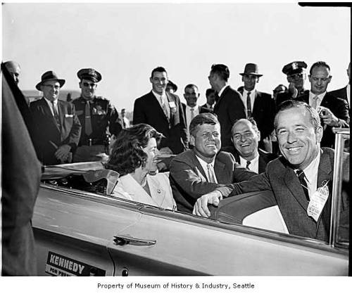 President John F. Kennedy and Others in Convertible, Seattle, 1961President Kennedy rode in a white convertible at the head of a parade of cars along Fourth Avenue as more than 50,000 people cheered his arrival in Seattle.  Seated with the Chief Executive is Governor Albert D. Rosellini and Senator Henry M. Jackson.Photographer: Seattle Post-Intelligencer Staff PhotographerDate:1961Image Number: 1986.5.31188.1To order a reproduction or to inquire about permissions contact photos@seattlehistory.org or phone us at 206-324-1126. Please refer to the Image Number and provide a brief description of the photograph.