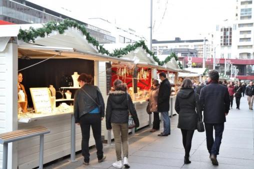 Passants devant les chalets du marché de Noël de Rennes