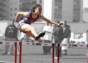 A woman jumping a hurdle