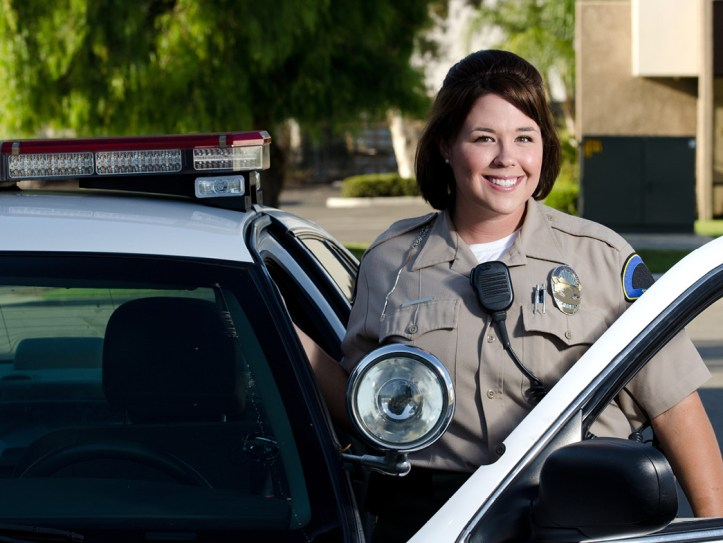 Police woman smiling next to her car