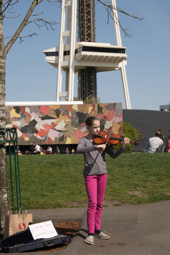 Young girl playing the violin and taking donations for music camp.