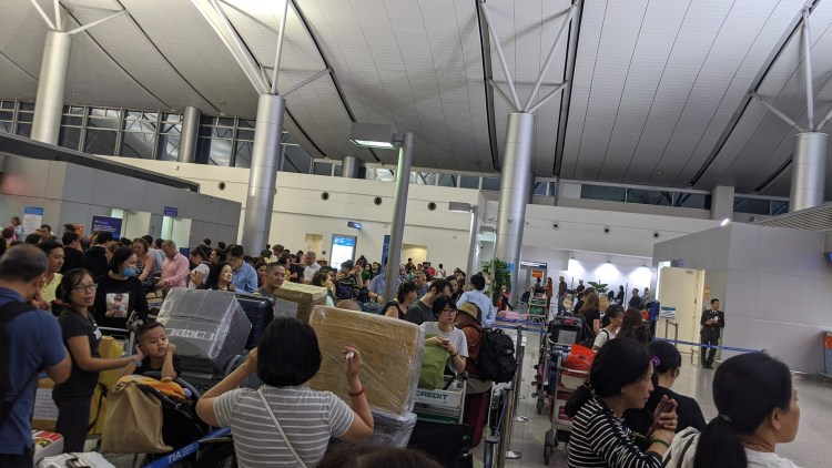 Queue at airport check-in counter. Image to illustrate queues
