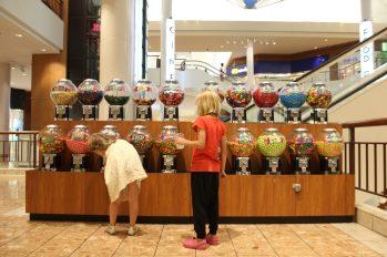 Signe och Vilja försöker skaka fram gratis godis i automater i en shoppinggalleria i St Louis