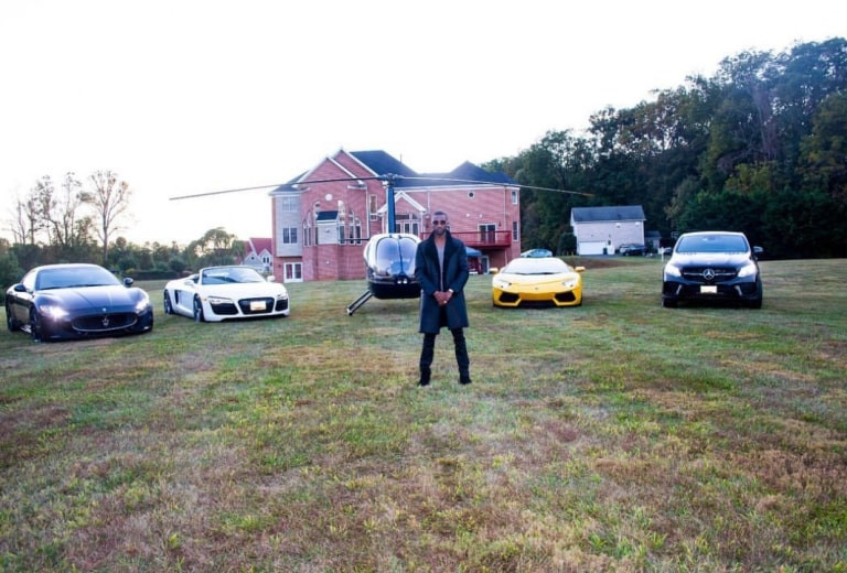 Passion Java poses next to his cars, helicopter