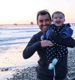 Chandler Walker holds his baby daughter on the beach.