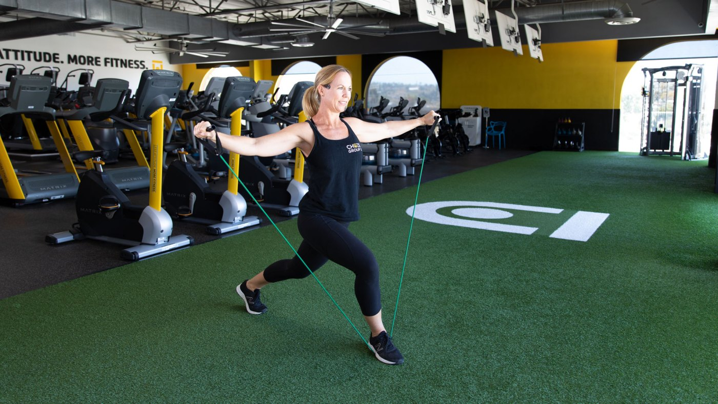 Instructor, Summer, teaching a resistance band workout on the turf area at Chuze Fitness for the virtual platform, iChuze Fitness.