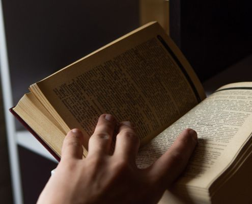 A hand holding a book open
