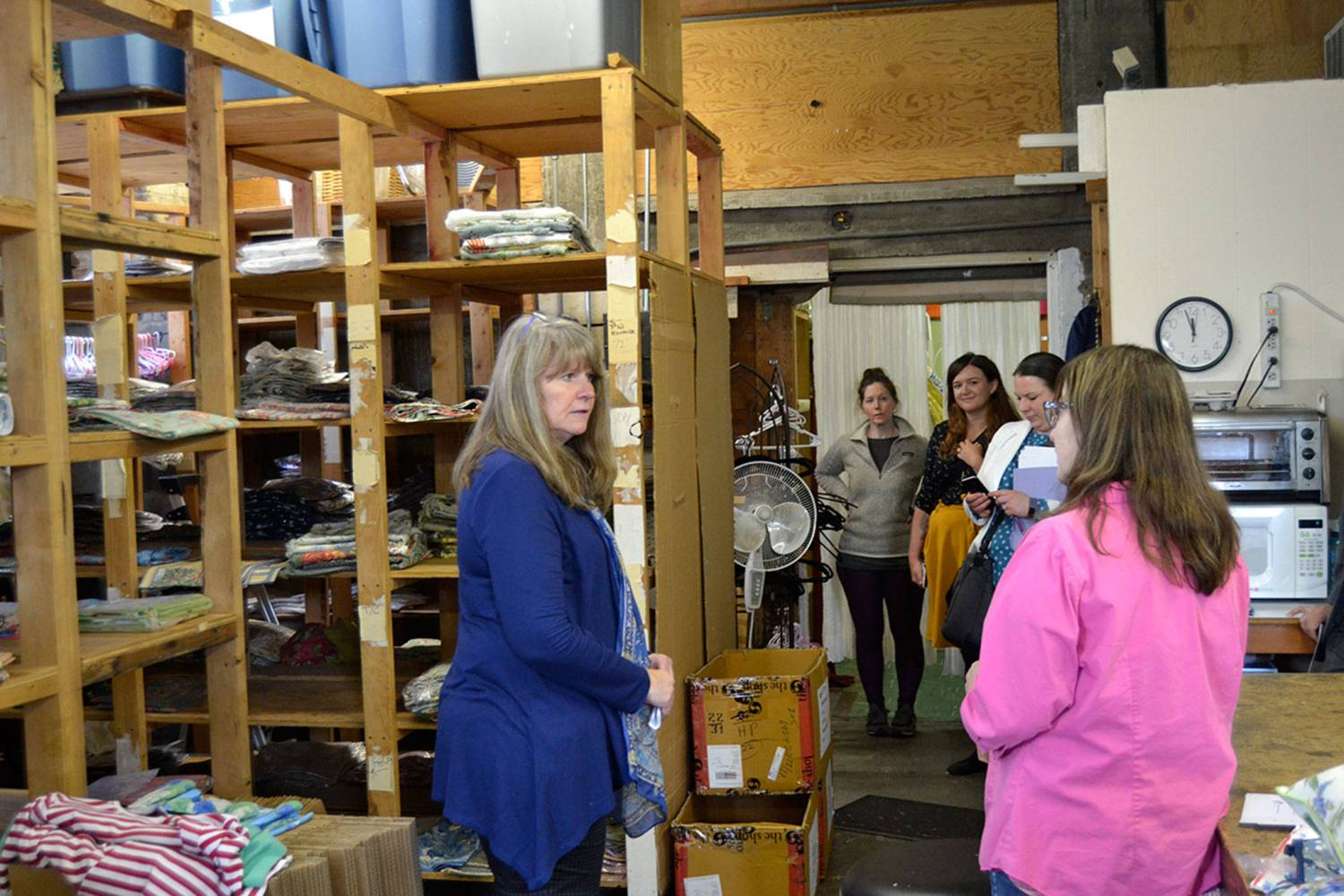 During a walking tour of some of Sequim's many small businesses, Kathy Greenwald, operations manager for Pondicherri/handprint, offers a behind-the-scenes look at the wholesale side of the business to U.S. Small Business Administration Seattle District Director Kerrie Hurd and others on March 28. Sequim Gazette photo by Matthew Nash