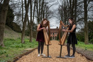 2 of Harps, two harpists playing two small harps on stands outside Port Lympne Hotel and Reserve in Kent