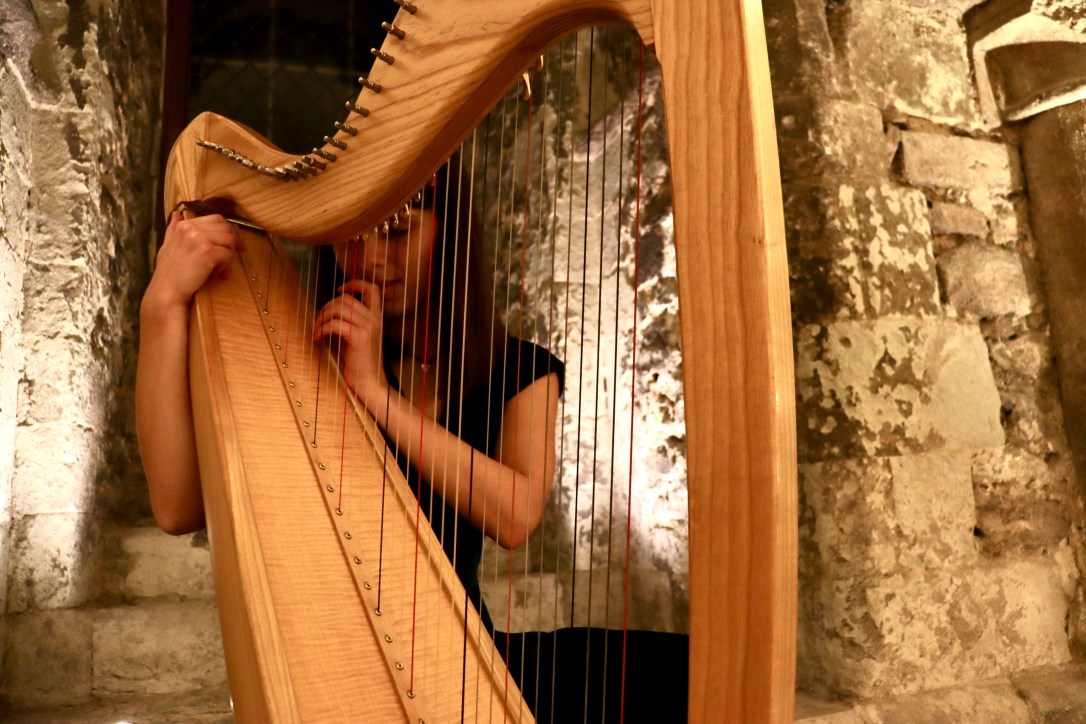 wedding harpist close to the harp, in historic cathedral