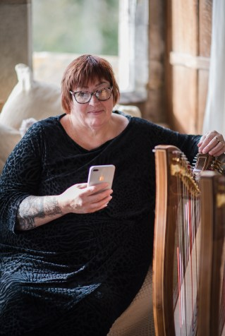 Janet Wilson, manager for 2 of harps holding an iPhone