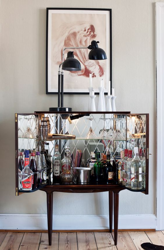 Wooden bar cart in the style of a case; glass-lined walls with diamond shape detail