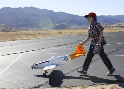 KAT MINER, SPECIAL TO THE HESPERIA STAR Nick Bennett, 11, pushes his P-51 Mustang from the runway on Saturday. Bennett, along with his grandfather, Bruce, is a member of the Victor Valley RC Flyers Club.