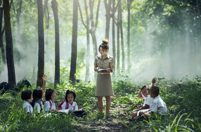 teacher and schoolkids in a forest