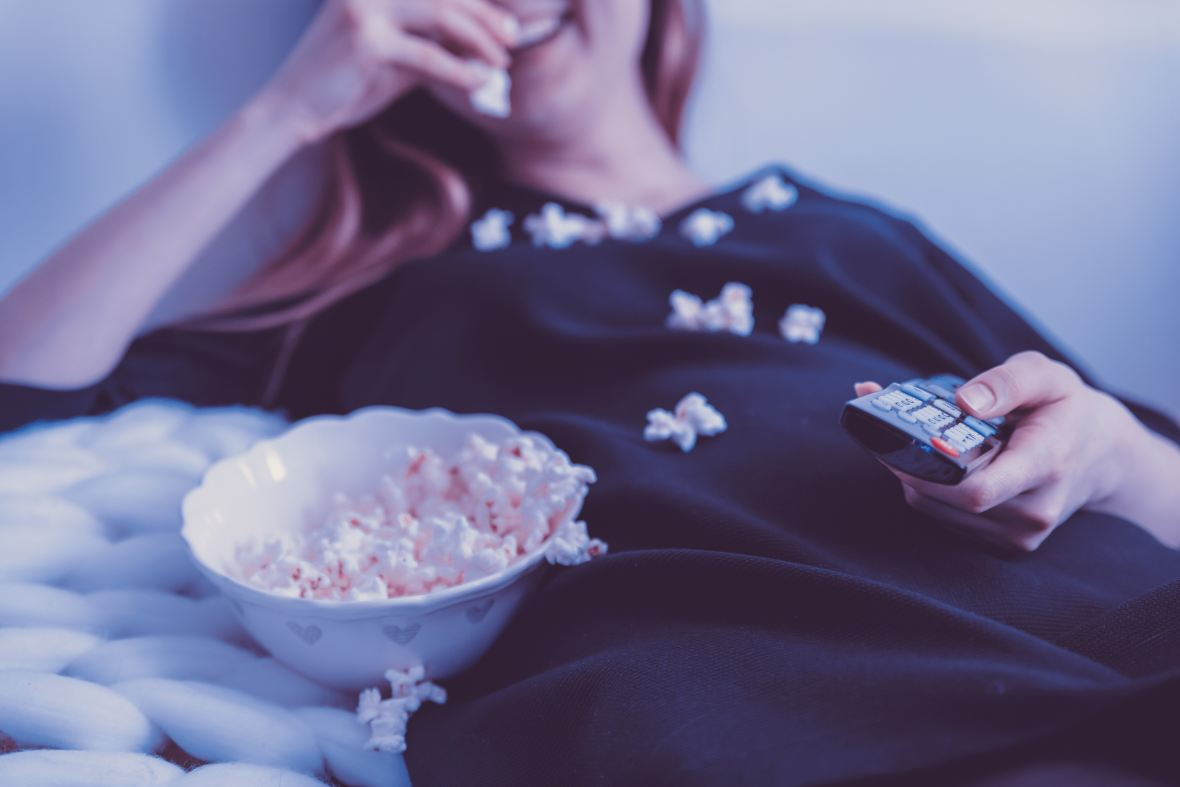woman eating popcorn holding remote control