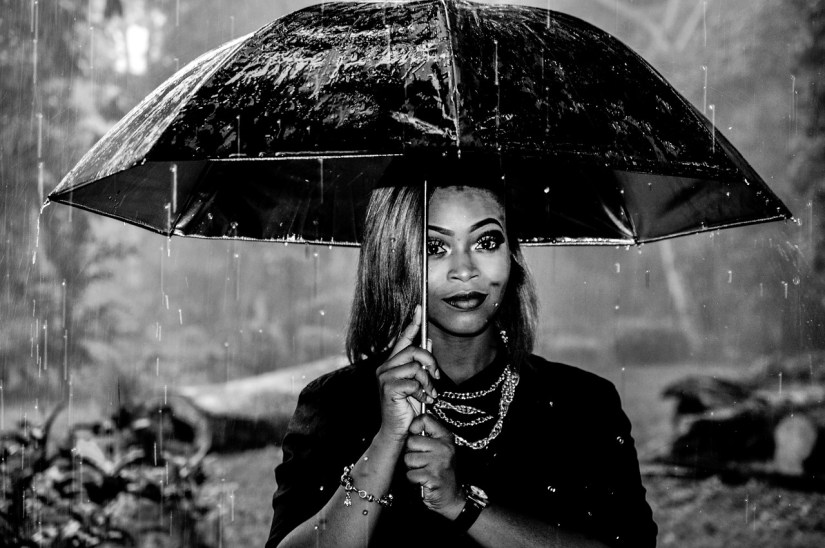 woman holding black umbrella in rain