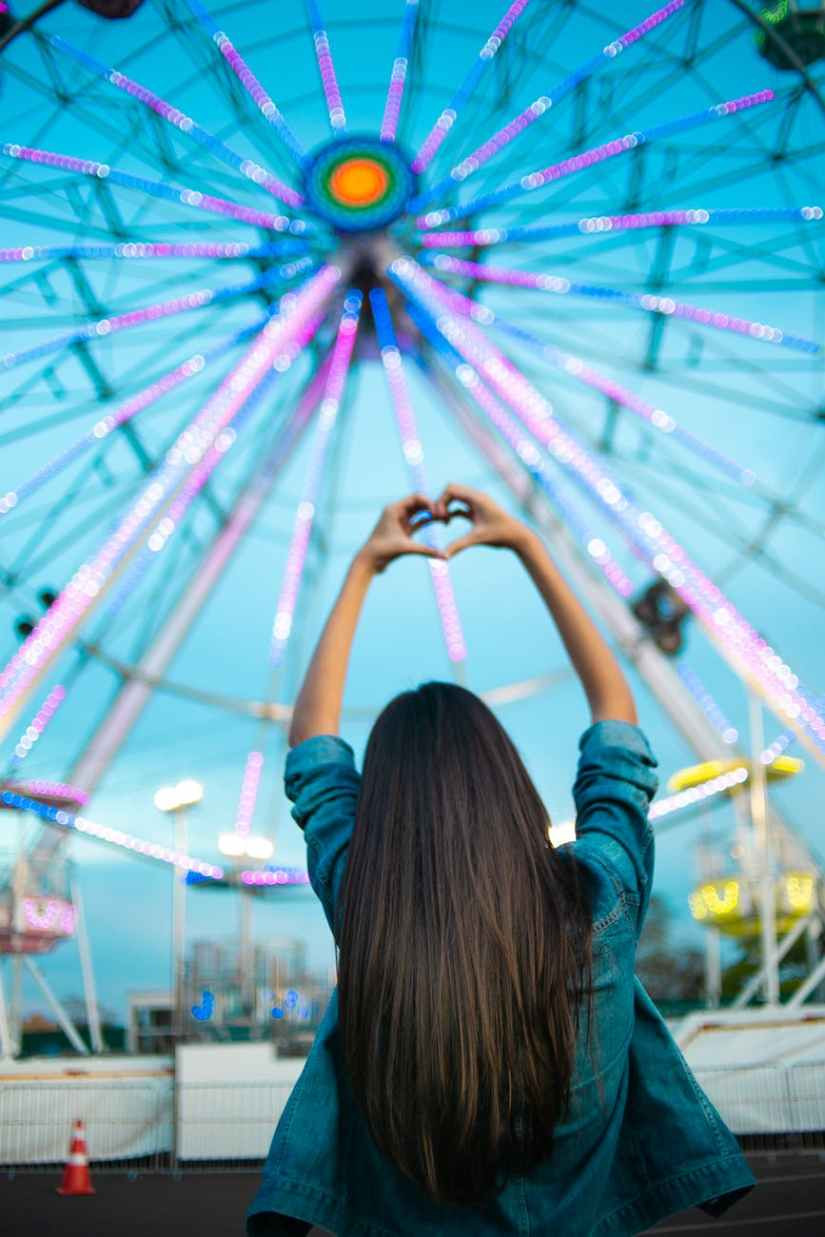 woman facing ferris wheel while making heart hand sign