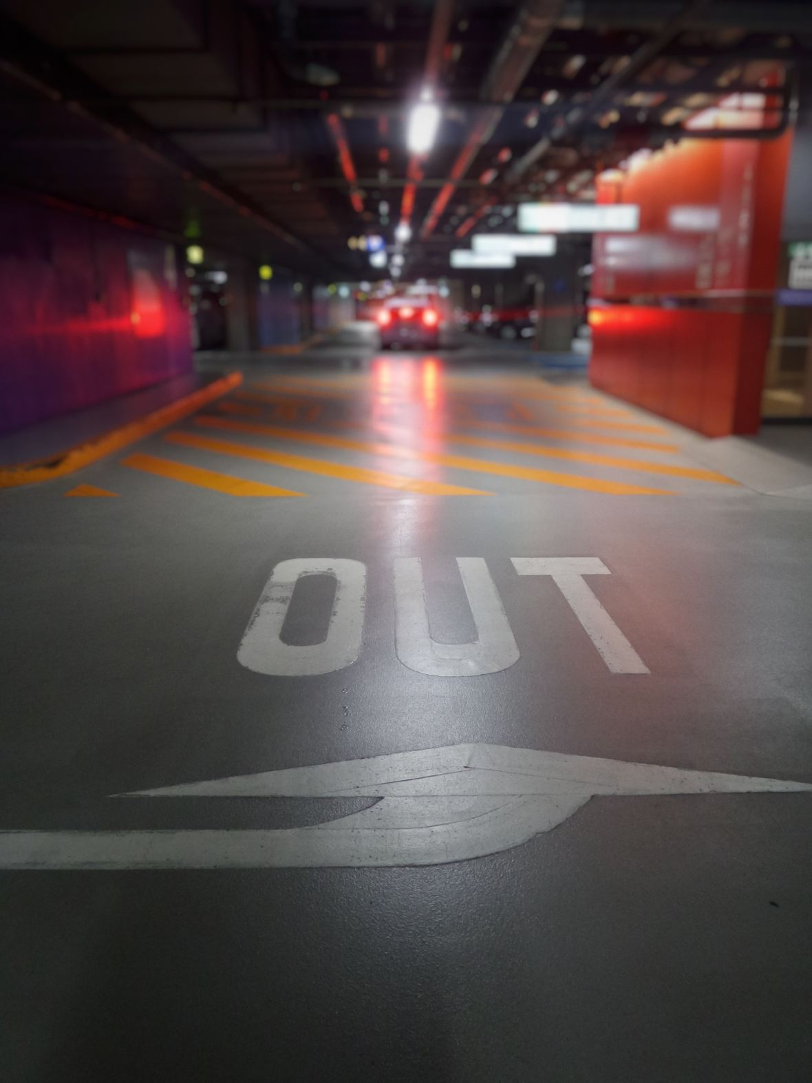 OUT sign painted on parking garage floor