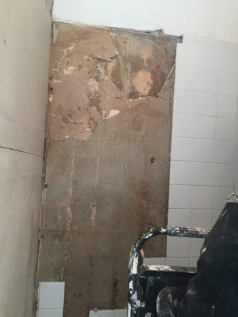 During -- Like so many older shower -- wall damage behind tile